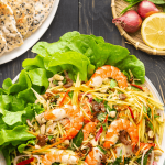 Vietnamese Mango Salad with a plate of sesame crackers and a collection of red shallots, lemon and Vietnamese coriander
