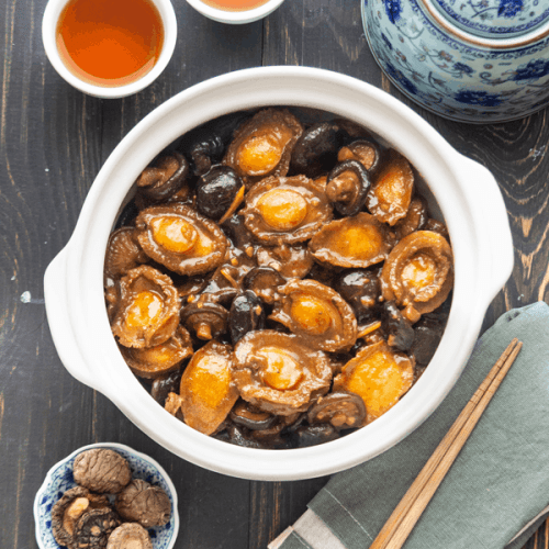 Braised Abalone with Mushrooms in a pot surrounded by a teapot, teacups with tea and a dish of mushrooms