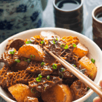 Braised Beef Honeycomb Tripe in a bowl with chopsticks holding one up
