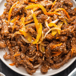 Rainbow Beef on a plate surrounded by a dish of sesame seeds and chopsticks