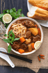 Bò Kho in a bowl with noodles surrounded by bean sprouts, Thai basil, chili, lemon and baguettes