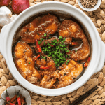 Cá Kho Tộ in a claypot surrounded by a dish of chili, chopsticks, a garlic bulb and red shallots
