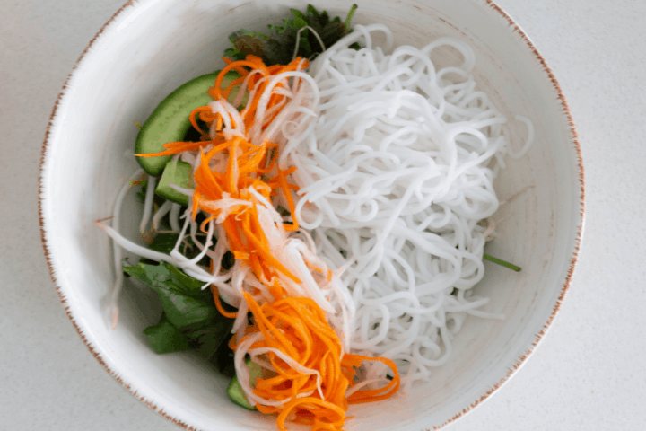 Pickled carrots and white radish in a bowl with noodles and salad
