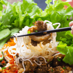 Chopsticks holding up noodes and pork over a salad