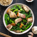Overhead shot of pork and greens stir fry in a bowl with chopsticks