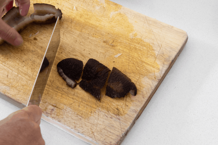 Sea cucumber cut into segments on a chopping board with a cleaver