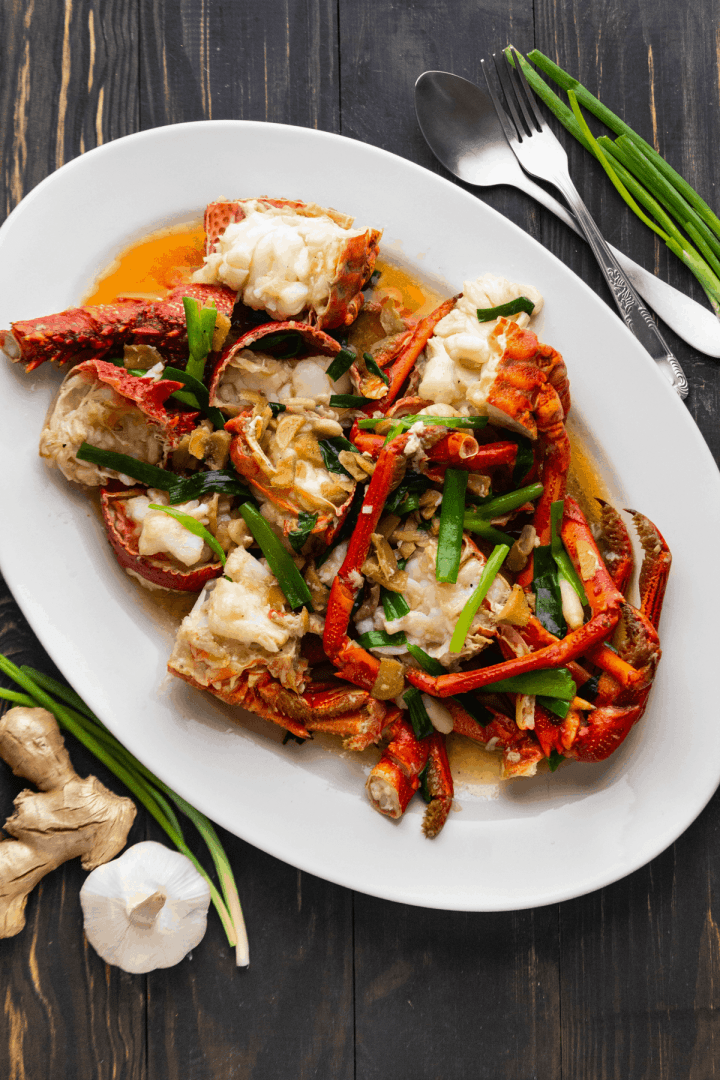Ginger Scallion Lobster on a plate surrounded by ginger, garlic and scallions.