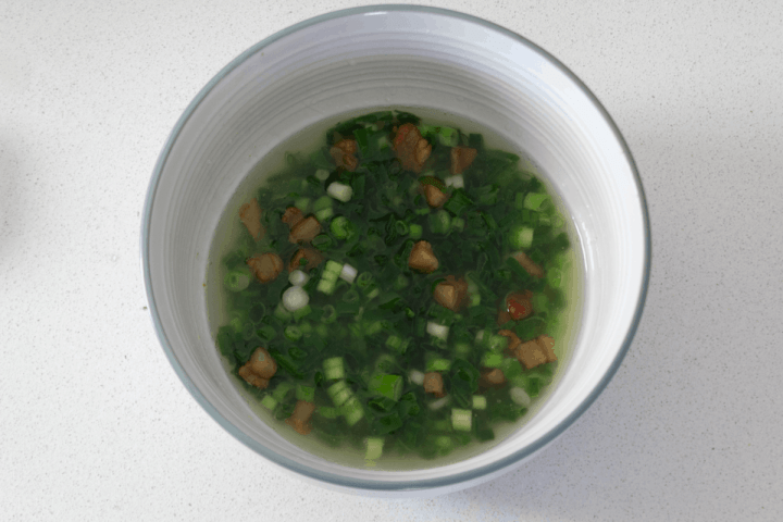 Spring onion oil in a bowl with fried lard pieces