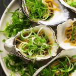Steamed oysters with ginger and shallots on a plate