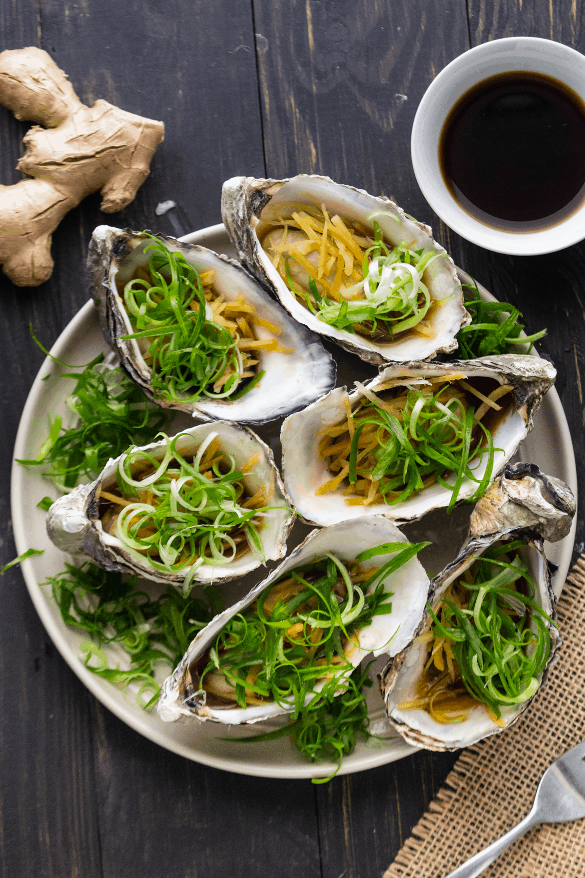 Steamed oysters with ginger and shallots on a plate with a dish of light soy sauce