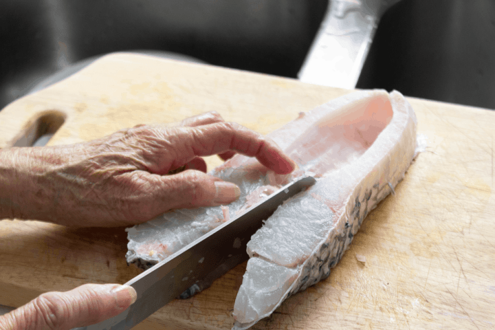 Hands holding a fish steak while a knife cuts through the center.