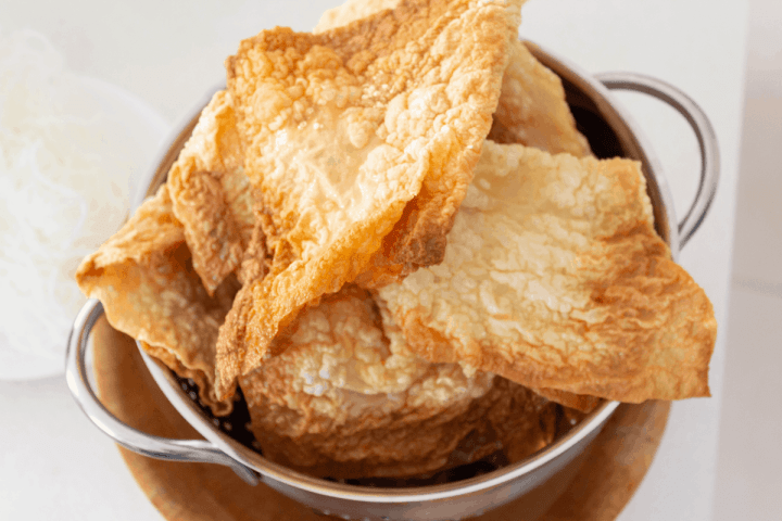 Fried bean curd sheets in a colander in a bowl.