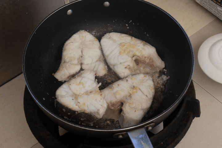 Fish steaks in oil in a wok.