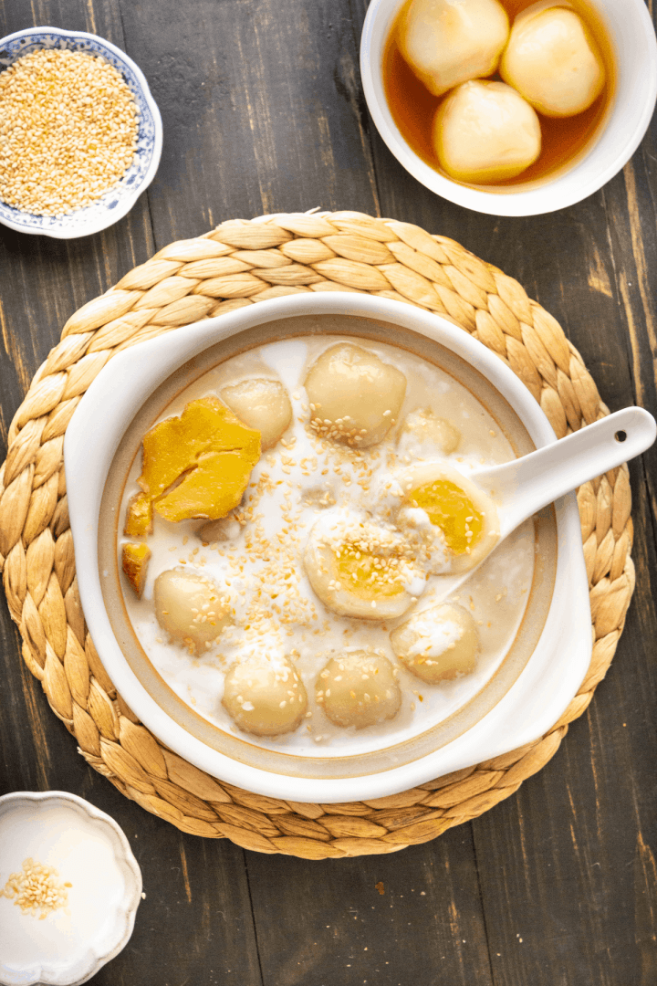 Vietnamese Glutinous Rice Balls in a bowl with a spoon in it surrounded by a dish of sesame seeds and a bowl of glutinous rice balls.