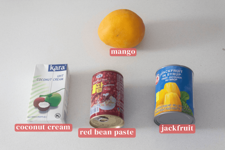 A mango along with a carton of coconut cream and cans of red bean paste and jackfruit.