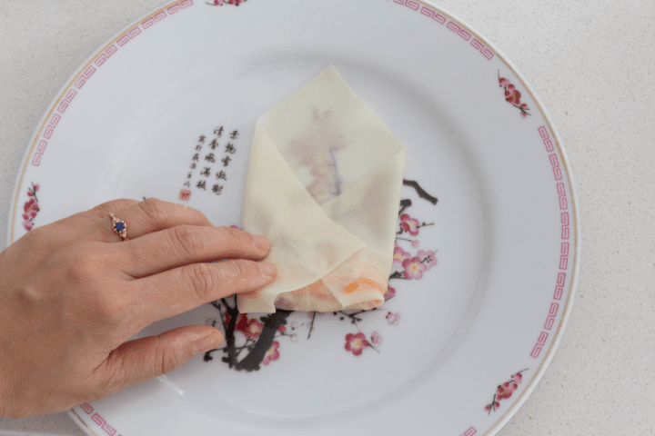 A hand pressing down on a spring roll half wrapped with its left and right corners folded in.