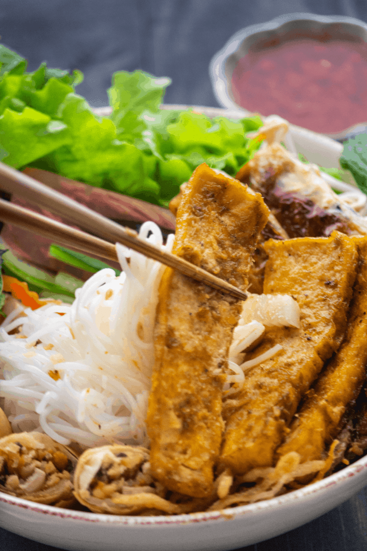 Noodles and fried tofu being held up by chopsticks in a bowl.