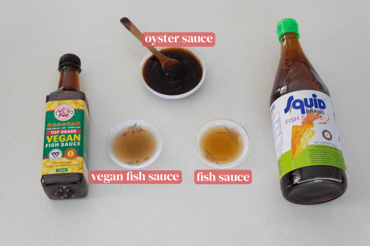 Oyster sauce and regular and vegan fish sauce in dishes along with their bottles.