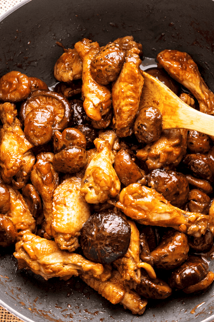 Braised Wings in a wok with a wooden spoon in it.