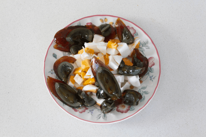 Chopped century and salted duck eggs on a plate.