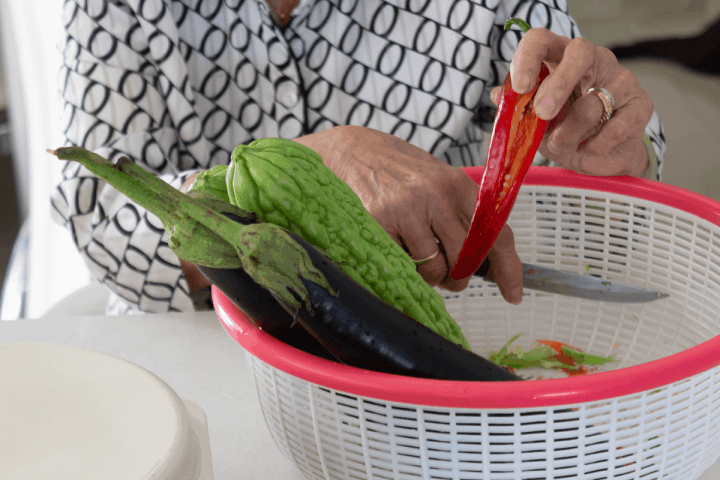 Hands holding a sliced open chili in a colander.