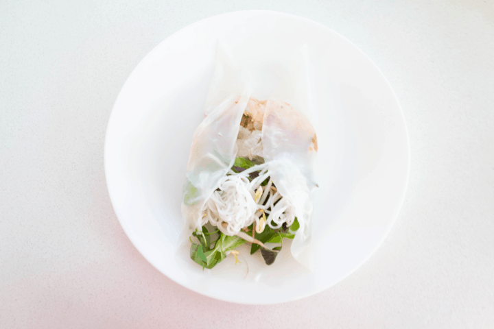 Rice paper sides folded into the midde over the filling on a plate.