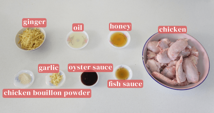 Wings in a dish along with oil, honey, fish sauce, oyster sauce, chopped garlic and chicken bouillon powder in dishes.