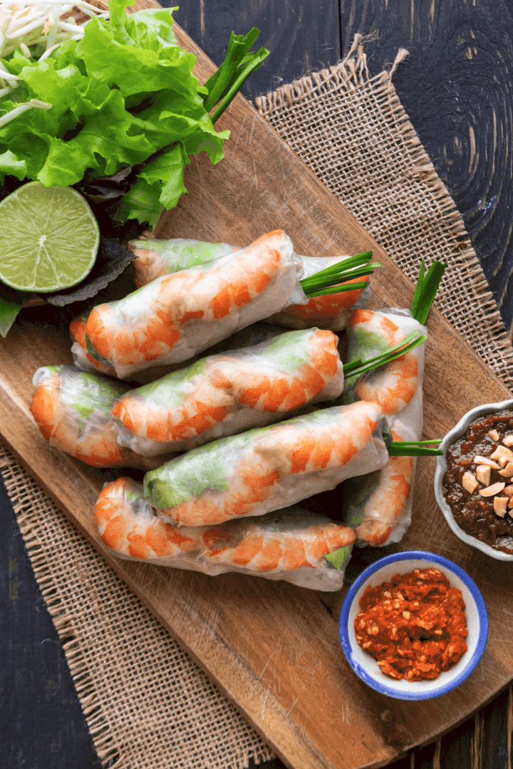Gỏi Cuốn on a board surrounded by herbs and sauces.
