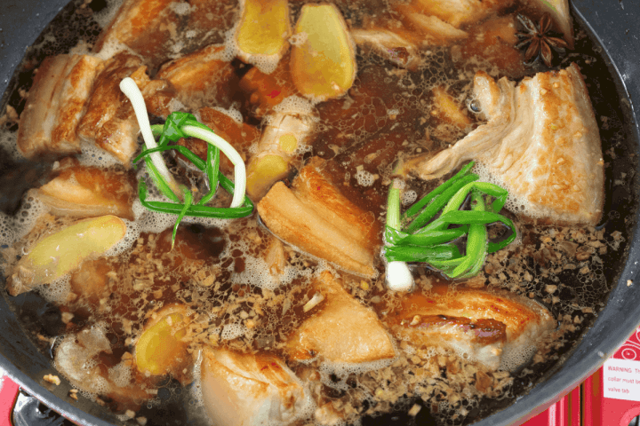 Pork belly simmering in liquid with aromatics.