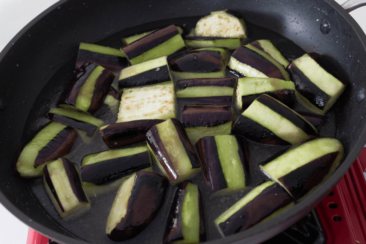 Eggplant pieces in water in a wok.