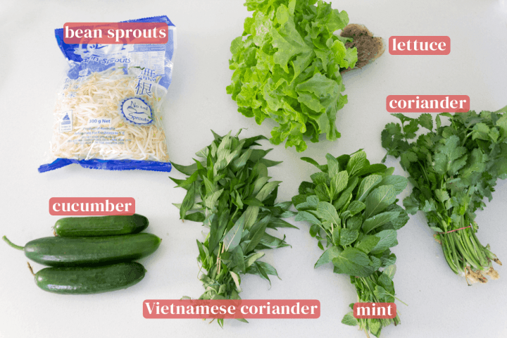 A bag of bean sprouts along with lettuce, Vietnamese coriander, mint, cucumber and coriander.