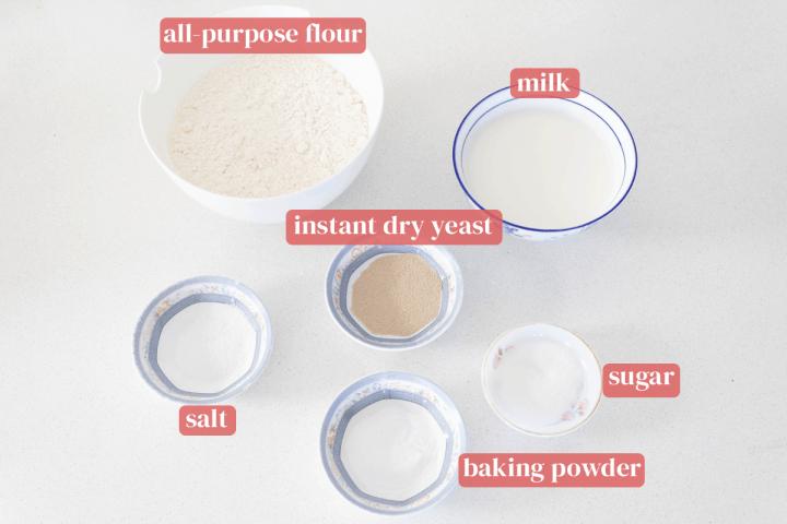Bowls of all-purpose flour, milk, instant dry yeast, salt, baking powder and sugar.