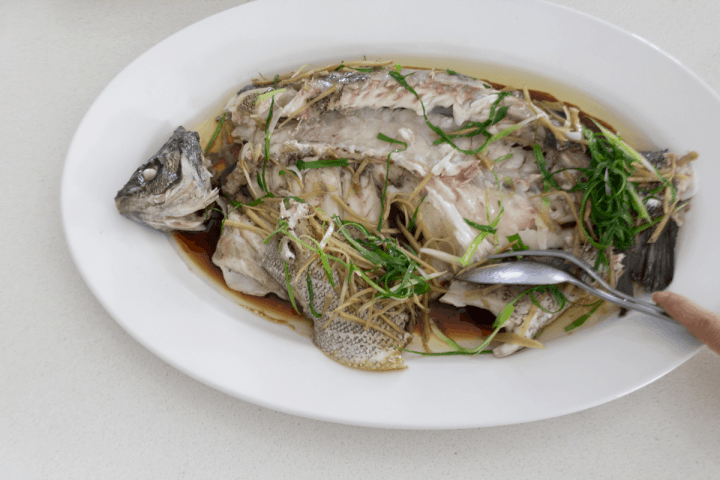A spoon pushing fish meat side on a plate.