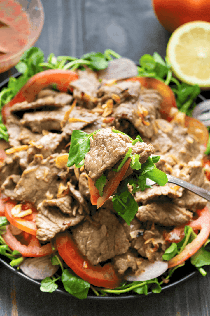 A fork holding up some Vietnamese Beef Salad.