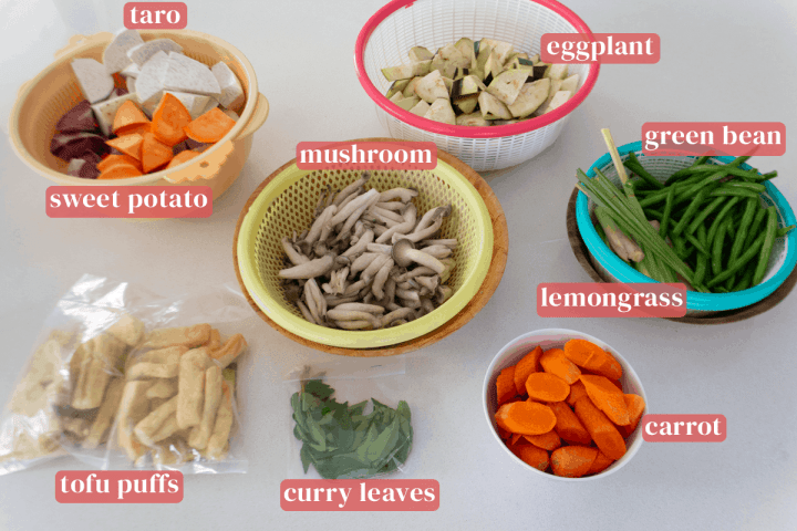 Colanders of sweet potato and taro chunks, eggplant pieces, lemongrass segments, mushroom and green beans along with a bowl of sliced carrots and bags of tofu puffs and curry leaves.