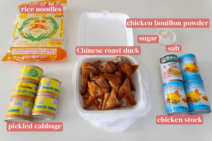 Rice noodles in a bag along with tinned pickled cabbage, a box of Chinese roast duck, tins of chicken stock and a dish of salt, sugar and chicken bouillon powder.