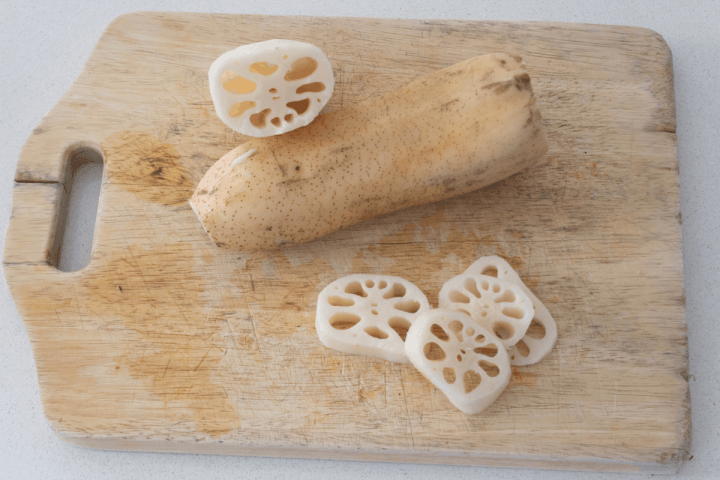 Lotus root slices and a whole lotus root on a board.