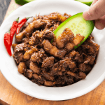 Thịt Kho Mắm Ruốc in a bowl with a hand dipping cucumber into it.