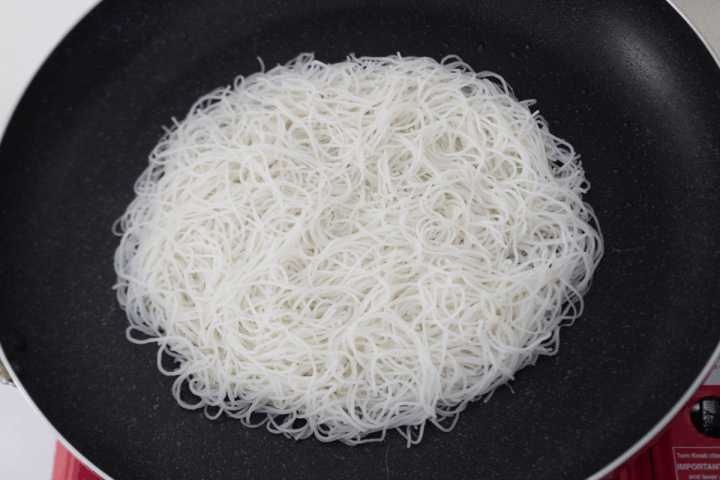 Rice noodles in a pan.