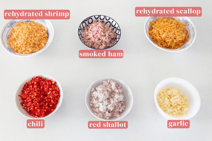 Bowls of finely chopped rehydrated shrimp, smoked ham, rehydrated scallops, garlic, red shallots and chili.