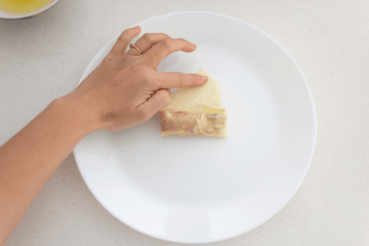 A hand spreading egg white on the tip of a spring roll opening on a plate.
