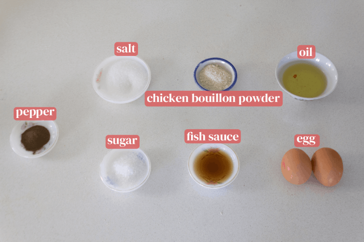Dishes of salt, sugar, chicken bouillon powder, pepper, fish sauce and oil along with two eggs.