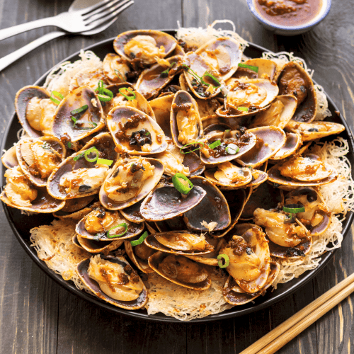 XO Pipis with Crispy Rice Noodles on a plate.