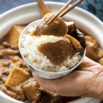 Braised Eggplant with Tofu in a claypot behind a hand holding a bowl of rice with eggplant pieces on it being held up by chopsticks.