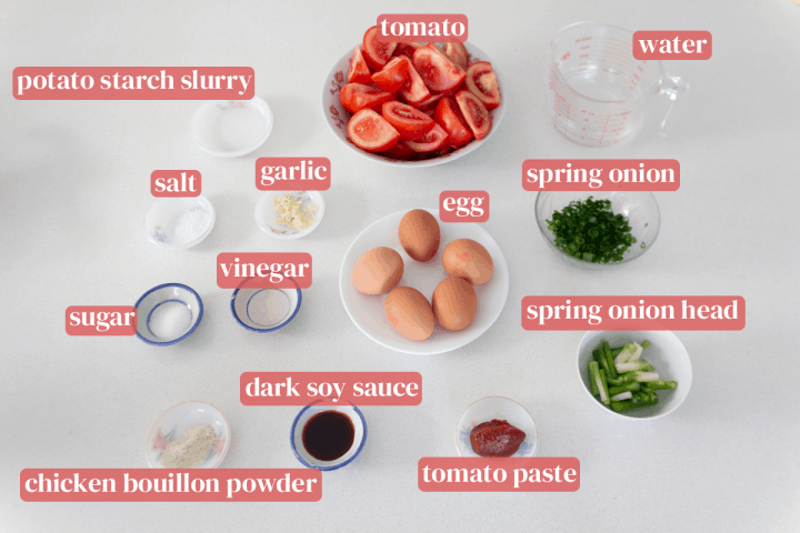 Bowls of quartered tomatoes, chopped spring onion and separated spring onion heads along with a plate of plates, dishes of tomato paste, dark soy sauce, chicken bouillon powder, vinegar, sugar, salt, chopped garlic and potato starch slurry next to a measuring jug of water.