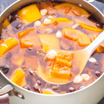 Papaya and Snow Fungus Dessert Soup in a pot with a ladle in it.
