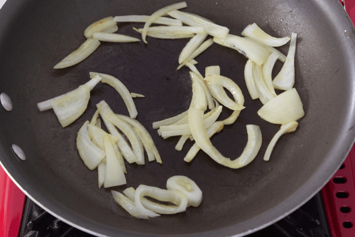 Sliced onion cooking in a pan.