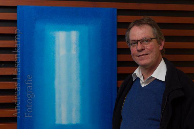 """Anfangs reichte eine Farbe: Thomas Schulz neben """"Blaue Meditation"""" von 2009. Foto: A. Hasenkamp, Fotograf in Münster."""