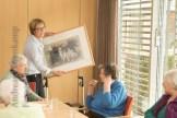 Mechtild Otte zeigt das Melk-Foto den Gästen im Saal des Achatius-Hauses. Foto: A. Hasenkamp, Fotograf in Münster.