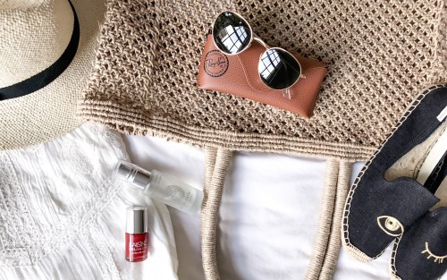 A straw hat, a beach tote, Ray Ban sunglasses, Soludos espadrilles, red nail polish and face mist are arranged in a flatlay   Wolf & Stag